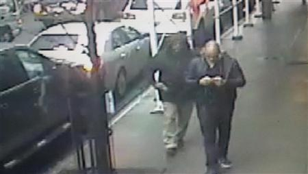 A gunman is seen pulling a weapon behind Brandon Lincoln Woodard (R) a moment before Woodward was shot in Manhattan, in this image taken from video and given to the media by the New York City Police Department, December 11, 2012. The shooter, who appears to be bald and may have a beard, exited a late model Lincoln sedan, initially bare-headed, but soon pulled the hood of his jacket over his head. REUTERS/New York City Police Department/Handout