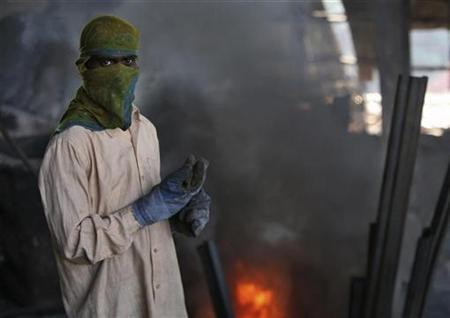 A labourer works inside a steel factory on the outskirts of Jammu December 3, 2012. REUTERS/Mukesh Gupta/files