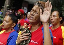 El presidente venezolano, Hugo Chávez, salió con éxito de la compleja operación que se le practicó el martes en Cuba para combatir el cáncer que padece y pasará varios días recuperándose, lo que deja en suspenso el futuro del líder socialista que debe asumir en menos de un mes un nuevo mandato. En la imagen, una mujer con un muñeco de Chávez en la mano en la vigilia por su salud en Caracas, el 11 de diciembre de 2012. REUTERS/Carlos García Rawlins