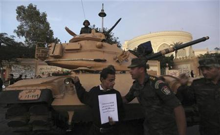 A Republican Guard officer asks an anti-Mursi protester to leave as he stands in front of a military tank outside the presidential palace in Cairo December 11, 2012. Egypt's army chief called for talks on national unity to end the country's deepening political crisis after a vital loan from the IMF was delayed and thousands of pro- and anti-government demonstrators took to the streets. The sign reads, ''The Brotherhood are criminals''. REUTERS/Amr Abdallah Dalsh (EGYPT - Tags: POLITICS CIVIL UNREST MILITARY)