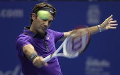 """El tenista suizo Roger Federer, quien visita Argentina por primera vez en su exitosa carrera, dijo el martes que no es ningún """"superhéroe"""" y se mostró sorprendido por la gran bienvenida que recibió. En la imagen, Federer devuelve una pelota a Jo-Wilfried en Sao Paulo, el 8 de diciembre de 2012. REUTERS/Stringer"""