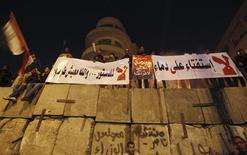 <p>Manifestants anti-Morsi devant le palais présidentiel du Caire. Le référendum sur le projet de nouvelle constitution en Egypte, prévu le 15 décembre, se déroulera sur deux jours et non plus sur la seule journée de samedi, a annoncé mardi soir la commission judiciaire chargée de surveiller le bon déroulement du scrutin. /Photo prise le 11 décembre 2012/REUTERS/Amr Abdallah Dalsh</p>
