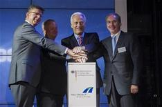 German Transport Minister Peter Ramsauer (2nd R), Reinhard Clemens of Deutsche Telekom (L), Toll Collect CEO Hanns-Karsten Kirchmann (2nd L) and Dieter Buhl of Daimler Financial Systems symbolically inaugurate the Toll Collect electronic toll collection system for heavy goods vehicles on German federal roads, at the Toll Collect headquarters in Berlin, August 1, 2012. REUTERS/Thomas Peter (GERMANY - Tags: POLITICS TRANSPORT BUSINESS)