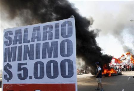 A placard that reads ''A minimum $ 5,000 wage'' is seen while demonstrators block the Pueyrredon Bridge, during a one-day nationwide strike in Buenos Aires November 20, 2012. REUTERS/Enrique Marcarian