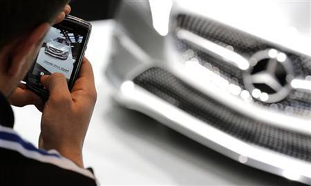 A man uses his cell phone to take pictures of the new Mercedes Concept Style Coupe car displayed on media day at the Paris Mondial de l'Automobile, September 28, 2012. The Paris auto show opens its doors to the public from September 29 to October 14. REUTERS/Christian Hartmann (FRANCE - Tags: TRANSPORT BUSINESS)