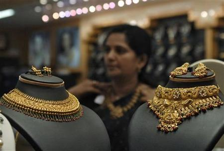 A woman tries on a gold necklace inside a jewellery shop in Hyderabad May 14, 2010. REUTERS/Krishnendu Halder/Files