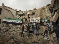 """Las potencias mundiales reunidas en Marrakech han reconocido la nueva coalición opositora de Siria como """"representante legítimo del pueblo sirio"""" y pidieron al presidente Bashar el Asad que """"se haga a un lado"""", según el borrador de una declaración obtenido el miércoles. En la imagen, manifestantes sostienen banderas de la oposición en una zona de edificios dañados tras un ataque con misiles de las fuerzas aéreas sirias, en Daraya, el 7 de diciembre de 2012. REUTERS/Kenan Al-Derani/Shaam News Network/Handout"""