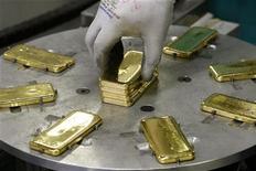 Рабочий кладет на конвейер слитки золота на фабрике в Мендризио (Швейцария), 13 ноября 2008 года. Золото дорожает накануне объявления итогов совещания Федеральной резервной системы, от которой рынок ждет дальнейших стимулирующих мер. REUTERS/Arnd Wiegmann