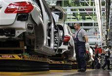 Employees of German car manufacturer Mercedes Benz work on Mercedes B-class cars at the Mercedes plant in Rastatt July 16, 2012. REUTERS/Alex Domanski