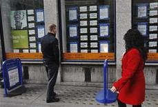 A man looks at adverts posted in the window of a recruitment agency in London March 14, 2012. REUTERS/Luke MacGregor
