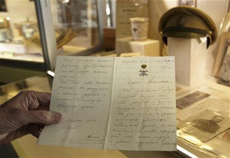 Prince Nicolas Romanov of Russia holds a letter signed 'Nicki' written by his ancestor Tsar Nicholas II during an auction preview in his apartment in Rougemont, 150 km (93.2 miles) east of Geneva, November 29, 2012. REUTERS/Denis Balibouse
