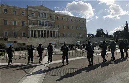 Police officers carry a security fence in front of the parliament in Athens December 7, 2012. REUTERS/John Kolesidis (GREECE - Tags: CIVIL UNREST POLITICS CRIME LAW)