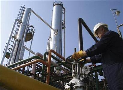 A worker adjusts the valve of an oil pipe at Samawa refinery in Samawa, 230 km (140 miles) south of Baghdad, in this file photo taken December 13, 2009. REUTERS/Ahmed Ameen