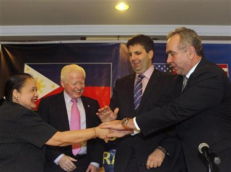 U.S. Assistant Secretary of State for East Asian and Pacific Affairs Kurt Campbell (R) joins hands with U.S. Assistant Secretary of Defense for Asian and Pacific Security Affairs Mark Lippert (2nd R), Philippines ambassador to the U.S. Jose Cuisia and Philippines Foreign Affairs Undersecretary for Policy Erlinda Basilio (L) during a joint news conference after their meeting at a hotel in Manila December 12, 2012. REUTERS/Cheryl Ravelo