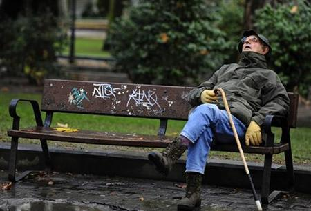 A man takes a nap at a park in Oviedo, November 30, 2012. REUTERS/Eloy Alonso