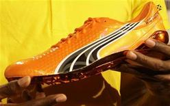 Sprinter Usain Bolt of Jamaica holds a Puma shoe during a news conference in Berlin, August 13, 2009. REUTERS/Tobias Schwarz (GERMANY SPORT ATHLETICS HEADSHOT)