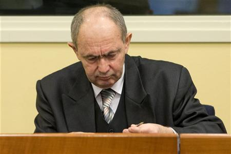 Zdravko Tolimir, a former high-ranking Bosnian Serb army officer charged with crimes including genocide in the 1995 Srebrenica massacre, holds a pen as he waits for the the Yugoslav war crimes tribunal to deliver its judgment in The Hague, December 12, 2012. REUTERS/Peter Dejong/ Pool