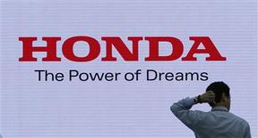 A man is silhouetted against a logo of Honda Motor at the company showroom in Tokyo in this October 23, 2012, file photo. Honda Motor Co will recall 871,000 vehicles that could roll away after the ignition key has been removed, including 807,000 in the United States, the company said on December 12, 2012. The automaker said a part in the ignition interlock could become damaged or worn, enabling the key to be removed even if the vehicle's transmission lever has not been shifted into park. REUTERS/Toru Hanai/Files