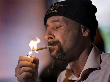 Christian Avarello from Italy lights up a joint purely made of marijuana in a coffeeshop in Amsterdam June 27, 2008. REUTERS/Michael Kooren