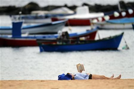 A woman reads a book as she enjoys the warm weather at Las Teresitas beach on the island of Tenerife in Spain's Canary Islands January 12, 2010. REUTERS/Santiago Ferrero