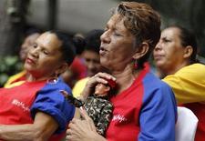 Sostenitori del presidente venezuelano Hugo Chavez con un bambolotto che lo raffigura. REUTERS/Carlos Garcia Rawlins