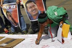 Um partidário do presidente da Venezuela, Hugo Chávez, escreve mensagens em um cartaz gigante em seu apoio em Caracas, Venezuela. 12/12/2012 REUTERS/Carlos Garcia Rawlins
