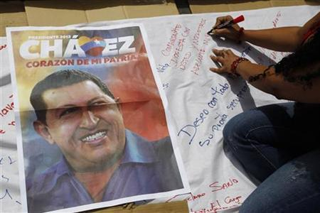 A supporter of Venezuelan President Hugo Chavez signs a giant poster in support of him in Caracas December 12, 2012. REUTERS/Carlos Garcia Rawlins