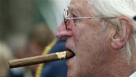 Disgraced British entertainer Jimmy Savile is seen arriving at the unveiling of a new monument, commemorating the fighter pilots who fought in the Battle of Britain, in London in this September 18, 2005 file photograph. REUTERS/Paul Hackett/Files