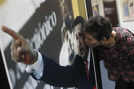 A supporter of Venezuela's President Hugo Chavez kisses a poster of him after a mass for his health and recovery at the Venezuelan embassy in Panama City December 12, 2012. REUTERS/Stringer
