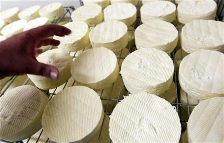 A worker checks French Camembert cheese in a cellar after the maturing process in the cheese dairy of La Ferme de la Heronniere in Camembert village, northwestern France, September 9, 2011. REUTERS/Regis Duvignau/Files