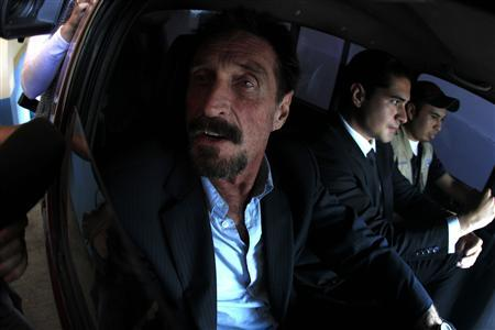 Software pioneer John McAfee is escorted by immigration officers to the Guatemalan Airport in Guatemala City December 12, 2012. REUTERS/Jorge Dan Lopez