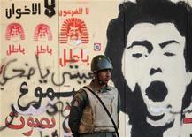 """Soldado é visto em frente a um grafite feito por manifestantes na parede do Palácio Presidencial, no Cairo. A oposição laica e liberal do Egito disse na quarta-feira que fará campanha pelo """"não"""" no referendo constitucional de sábado, desistindo de boicotar a votação, desde que haja salvaguardas para um processo justo. 12/12/2012 REUTERS/Khaled Abdullah"""