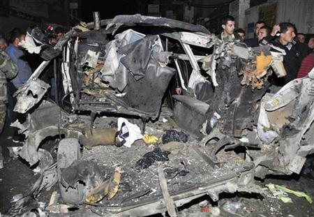 A crowd gathers around wrecked vehicles after a bomb explosion in a minibus at the Mazeh 86 area in Damascus in this December 12, 2012 handout photograph released by Syria's national news agency SANA. REUTERS/SANA
