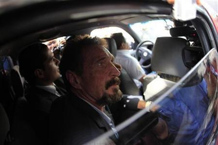 Software pioneer John McAfee is escorted by immigration officers to the Guatemalan Airport in Guatemala City December 12, 2012. REUTERS/Jorge Lopez