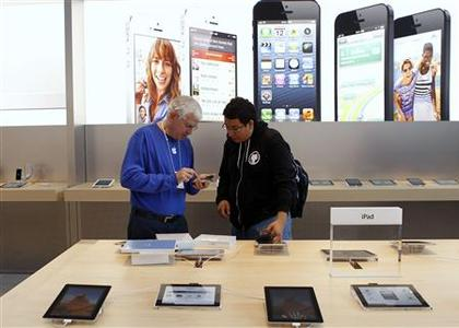 A customer is helped by an Apple employee while looking over the iPad mini after the device went on sale at Apple's retail store in Palo Alto, California in this November 2, 2012 file photograph. REUTERS/Robert Galbraith/Files