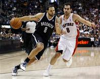 Brooklyn Nets Deron Williams drives to the net past Toronto Raptors Jose Calderon during the second half of their NBA basketball game in Toronto, December 12, 2012. REUTERS/Mark Blinch