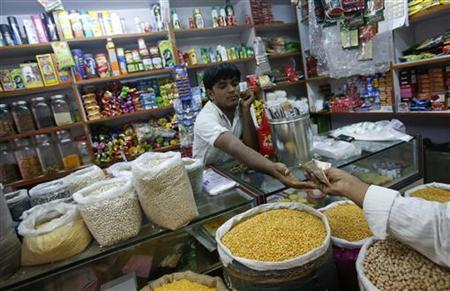 The owner of a ''Kirana'' or mom-and-pop grocery store accepts money from a customer in his shop in Mumbai December 7, 2012. REUTERS/Vivek Prakash