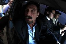 Джон Макафи едет в аэропорт Гватемалы в сопровождении сотрудников миграционной службы, 12 декабря 2012 года. Депортированный из Гватемалы создатель популярного антивируса Джон Макафи вернулся в Майами, сообщили летевшие с ним пассажиры борта American Airlines. REUTERS/Jorge Dan Lopez