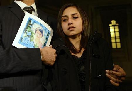 Lisha Barboza reacts as she stands with her father Ben while he holds a picture of his wife, nurse Jacintha Saldanha, as they leave the Houses of Parliament in London December 10, 2012. REUTERS/Dylan Martinez