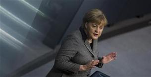 German Chancellor Angela Merkel delivers a government policy statement before the German lower house of parliament, the Bundestag, in Berlin, December 13, 2012. The streaks are created by reflections in a metal railing. REUTERS/Thomas Peter (GERMANY - Tags: POLITICS)