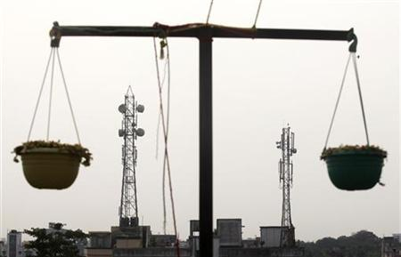 Telecommunication towers are pictured through hanging flower pots at a residential building in Kolkata December 11, 2012. REUTERS/Rupak De Chowdhuri