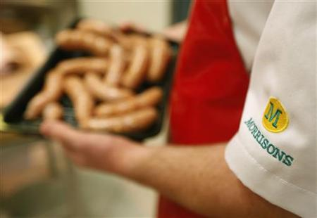 A Morrisons supermarket butcher carries a tray of sausages at a store in London November 21, 2012. REUTERS/Luke MacGregor