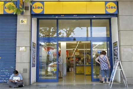 A woman begs next to the Lidl supermarket entrance in Barcelona July 14, 2012. REUTERS/Albert Gea