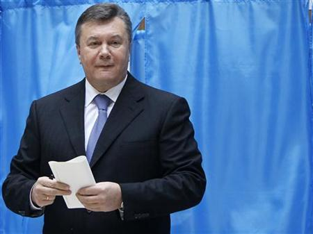 File photo of Ukrainian President Viktor Yanukovich holding his ballot as he visits a polling station during the parliamentary elections in Kiev, October 28, 2012. REUTERS/Gleb Garanich