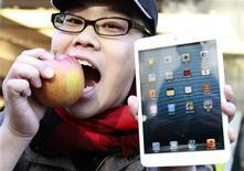 Koudai Taguchi morde maçã e mostra seu novo iPad mini diante de loja da Apple, em Tóquio. As ações da Apple podem estar em queda devido às preocupações dos investidores quanto à concorrência crescente que a empresa enfrenta, mas visitas a lojas e entrevistas com compradores de tablets e smartphones nos dez últimos dias sugerem que os consumidores de todo o mundo não compartilham muito dessa visão negativa. 2/11/2012 REUTERS/Yuriko Nakao