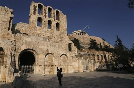 A woman takes photographs outside of the ancient Herodes Atticus theatre as the Parthenon temple is seen in the background in Athens December 13, 2012. REUTERS/John Kolesidis