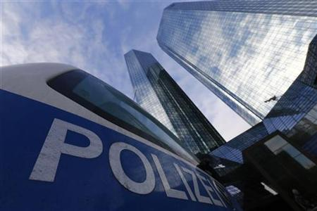 Police vehicles are parked outside the headquarters of Germany's largest business bank, Deutsche Bank AG in Frankfurt December 12, 2012. REUTERS/Kai Pfaffenbach (GERMANY - Tags: BUSINESS CRIME LAW TPX IMAGES OF THE DAY)