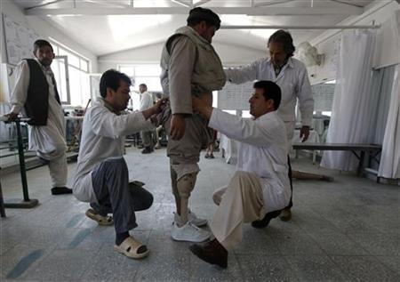 Afghan doctors adjust a prosthetic leg of a man at an ICRC hospital for war victims at the Orthopedic Center of the International Committee of the Red Cross in Kabul April 11, 2012. REUTERS/Omar Sobhani/Files