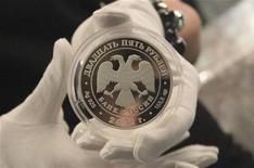 Монета достоинством 25 рублей на презентации в Москве 25 апреля 2012 года. Рубль подешевел в четверг на фоне снижения предложения валюты от компаний-экспортеров, из-за смещения фокуса внимания глобальных рынков на нерешенные бюджетные проблемы США с новых стимулирующих мер ФРС, что привело к сокращению спроса на рискованные активы. REUTERS/Yana Soboleva