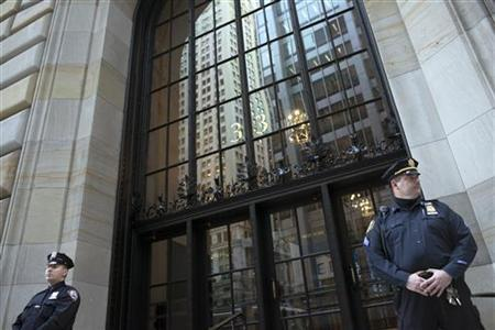 Federal Reserve and New York City Police officers stand guard in front of the New York Federal Reserve Building in New York, October 17, 2012. REUTERS/Keith Bedford